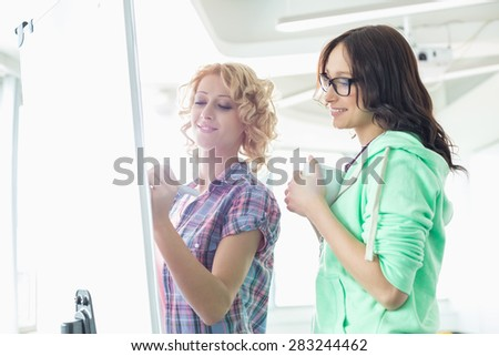 Smiling businesswomen preparing presentation on whiteboard in creative office - stock photo