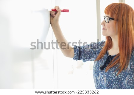 Smiling businesswomen writing on whiteboard in creative office - stock photo