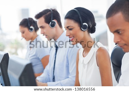 Smiling call center employees sitting in line with their headset - stock photo