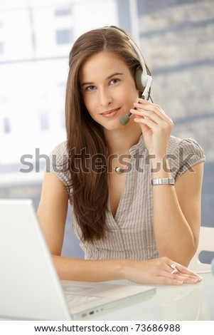 Smiling call center operator girl sitting at desk with laptop computer using headset, looking at camera.? - stock photo