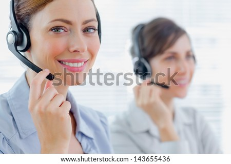 Smiling call centre agents with headsets at work in an office - stock photo