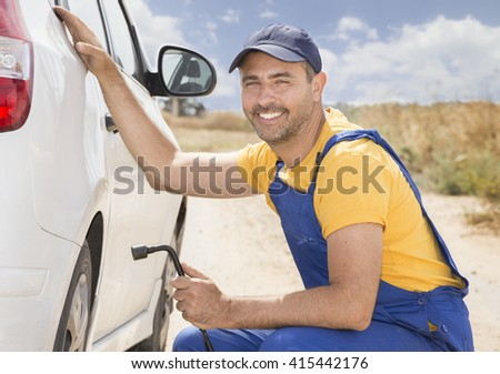 Smiling Car mechanic in uniform replaces a wheel of a stuck car in the middle of the wilderness. road services insurance concept. - stock photo