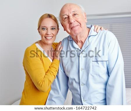 Smiling caregiver nursing senior man in family at home - stock photo