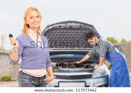 Smiling careless female holding a key while in the background mechanic is checking her car