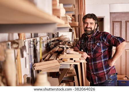 Smiling carpenter and small business owner, looking at the camera, while standing confidently in his workshop with shelves of wooden planks  - stock photo