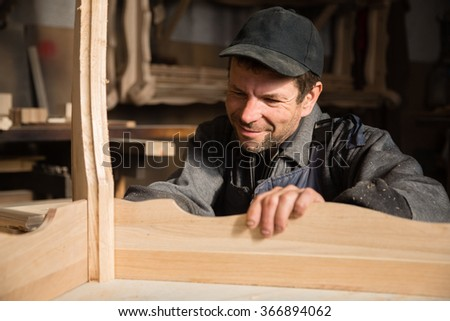 Smiling carpenter examines produces furniture in the workshop