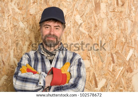 Smiling carpenter on a background sheet of plywood - stock photo