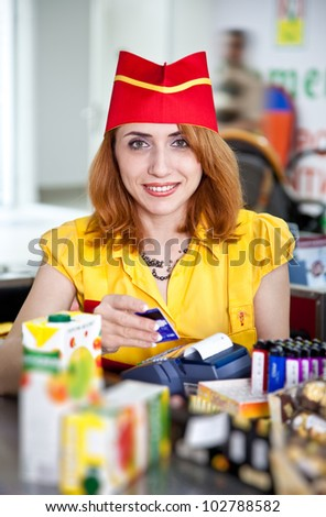 Smiling cashier girl in red and yellow uniform in supermarket - stock photo