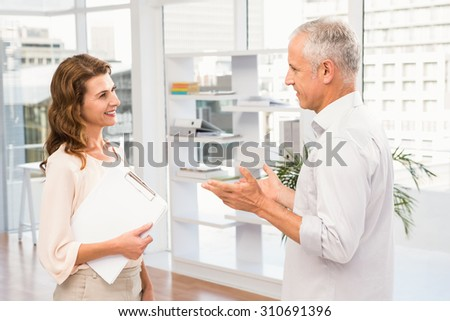 Smiling casual business colleagues talking in the office - stock photo