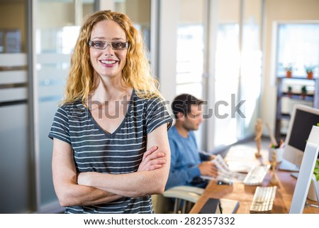 Smiling casual businesswoman posing with her partner behind in the office - stock photo