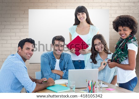 Smiling casual colleagues in a meeting against white wall - stock photo