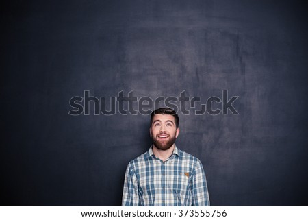 Smiling casual man looking up at copyspace over black background - stock photo