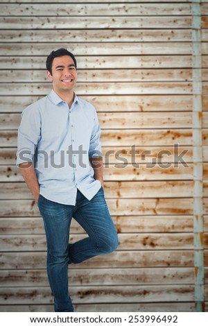 Smiling casual man standing against faded pine wooden planks - stock photo