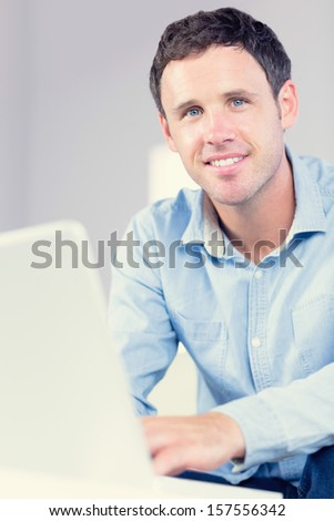 Smiling casual man using laptop looking at camera in bright living room