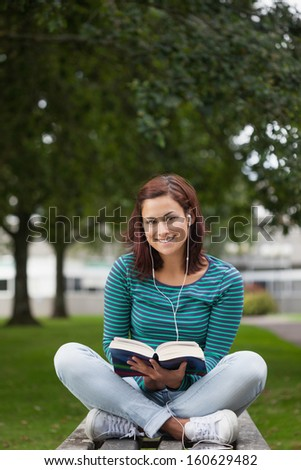 Smiling casual student sitting on bench reading on campus at college - stock photo