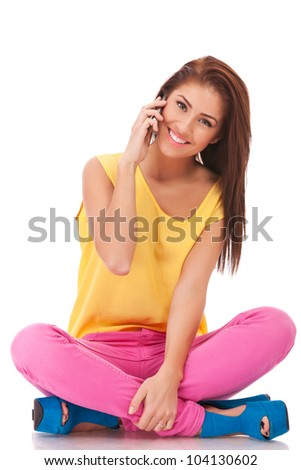 smiling casual woman is sitting and talking on  mobile phone isolated on white - stock photo
