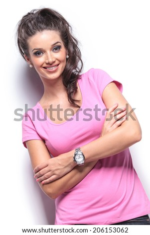smiling casual woman with hands crossed staning in studio