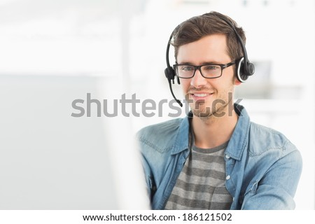Smiling casual young man with headset using computer in a bright office - stock photo