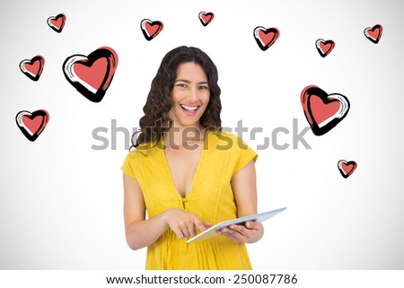 Smiling casual young woman scrolling on her tablet computer against white background with vignette - stock photo