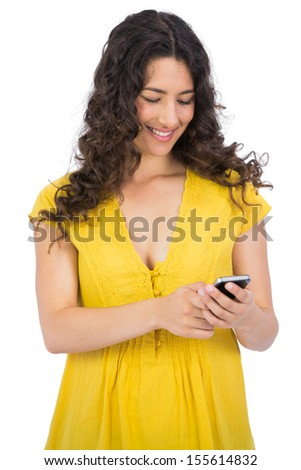 Smiling casual young woman texting on her phone on white background