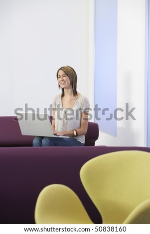 Smiling, casually dressed Businesswoman sitting on sofa, Using laptop
