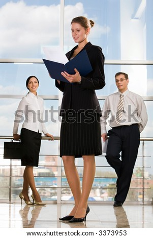 Smiling Caucasian businesswoman reading documents in modern office building and two businesspeople on the background - stock photo