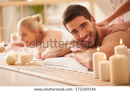 Smiling Caucasian couple enjoying a back massage. - stock photo