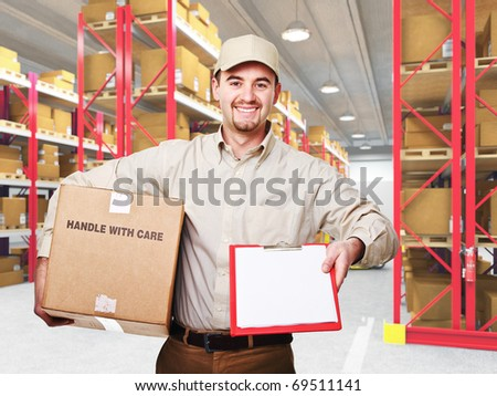 smiling caucasian delivery man and 3d warehouse background - stock photo