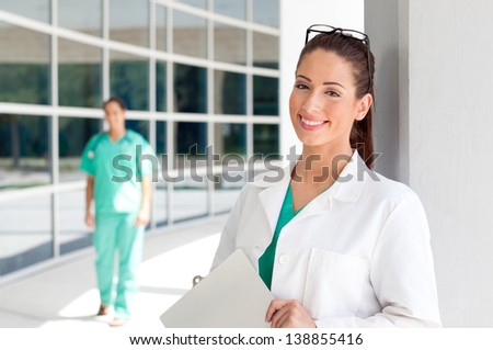 Smiling Caucasian doctor holding a clipboard in brightly lit exterior hospital environment in scrubs, white lab coat. Nurse in scrubs in the background. - stock photo