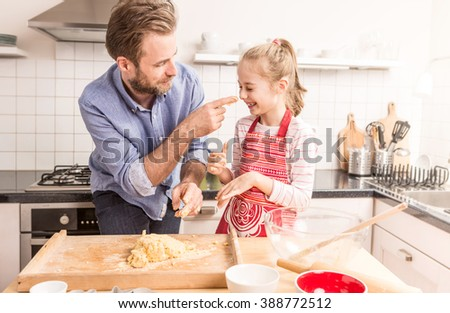 Smiling caucasian father and daughter having fun while preparing cookie dough in the kitchen. Baking - happy family time. - stock photo