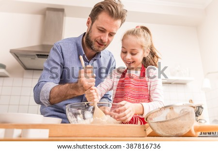 Smiling caucasian father and daughter preparing cookie dough in the kitchen. Baking - happy family time. - stock photo