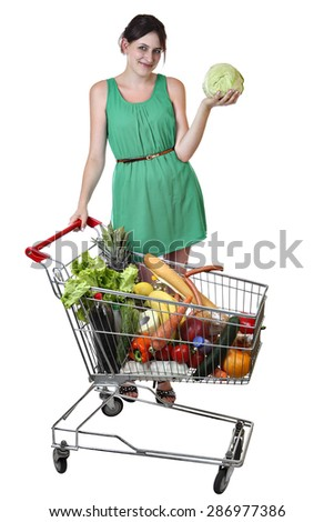 Smiling Caucasian girl in a green dress 19 years old holding a cabbage standing near a shopping cart filled with food isolated on a white background, saved path selection. - stock photo