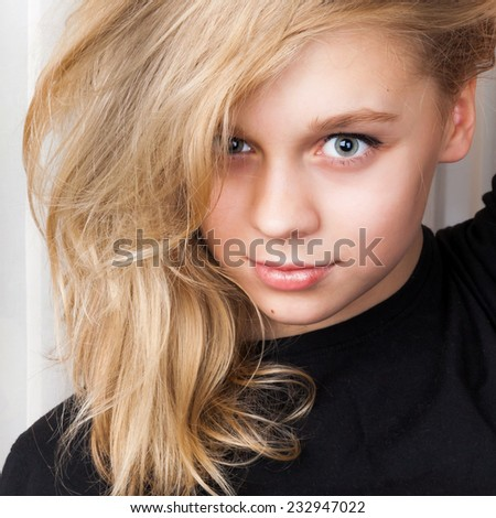 Smiling Caucasian girl with long blond hair, closeup studio portrait - stock photo