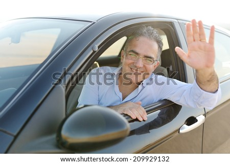 smiling caucasian man sitting in his new car - stock photo