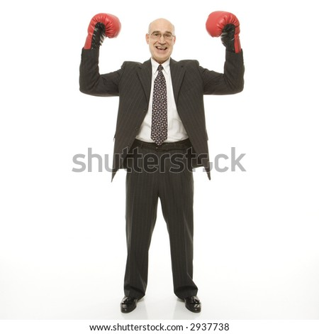 Smiling Caucasian middle-aged businessman standing with arms raised wearing boxing gloves. - stock photo