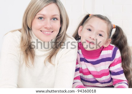 Smiling caucasian mother lying on the floor with her daughter and looking at camera