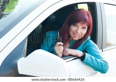 Smiling caucasian red-haired young woman sitting in a car and demonstrating the keys - stock photo