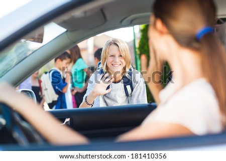 Smiling Caucasian schoolboy waving goodbye to his mother before school. - stock photo