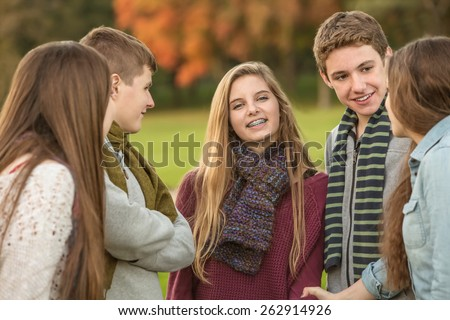 Smiling Caucasian teen female with group of friends - stock photo
