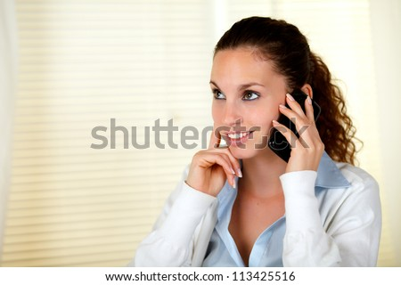Smiling caucasian woman conversing on cellphone while looking up - copyspace - stock photo