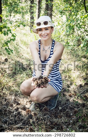 Smiling caucasian woman enjoying the pine cones in the forest by summer. Natural beauty. - stock photo