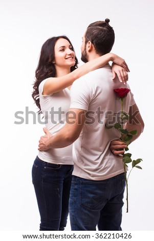 Smiling caucasian woman hugging her boyfriend and holding the rose she got for Valentine's Day. - stock photo
