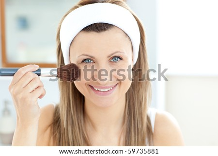 Smiling caucasian woman putting powder on her face smiling at the camera in the bathroom at home - stock photo