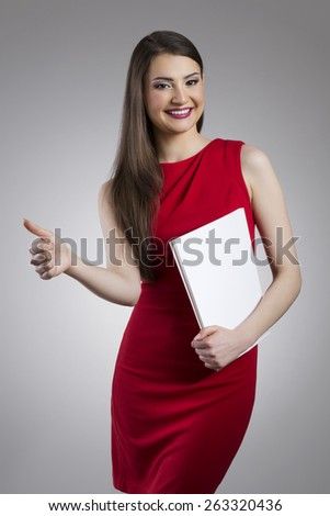 Smiling CEO in red dress holding white folder and showing okay gesture - stock photo