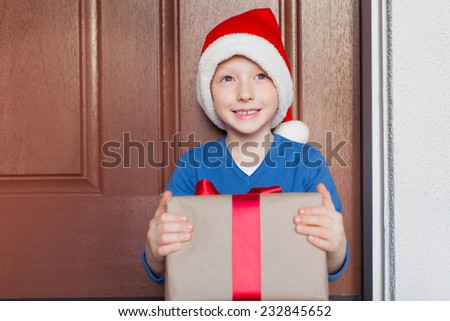smiling cheerful boy with christmas present by the decorated house - stock photo