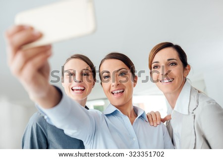 Smiling cheerful business women taking a selfie in the office using a smart phone