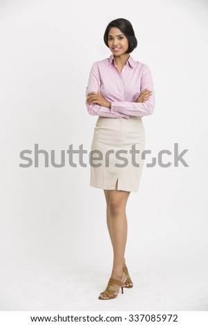 Smiling cheerful businesswoman with her arms crossed standing on white background. - stock photo
