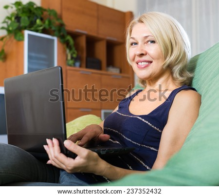 smiling cheerful  mature woman using laptop on sofa in home