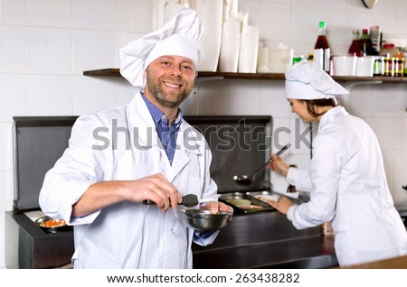 Smiling  chef and cook  working at take-away restaurant kitchen