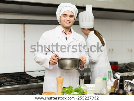 Smiling chef and his assistant preparing meal in restaurant. Focus on man - stock photo